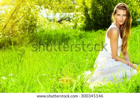 Beautiful young woman in light white dress sitting on a grass in the summer park.  - stock photo