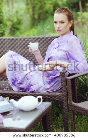 Beautiful young woman in lilac dress drinking tea and resting in the garden in sunny day