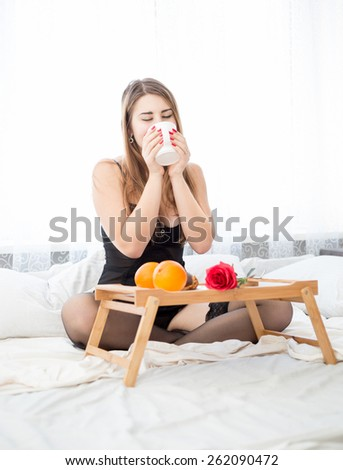 Beautiful young woman in lingerie having breakfast at morning - stock photo