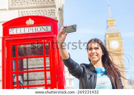 Beautiful young woman in London taking a selfie with Big Ben and red phone booth on background. She is holding the phone with right hand and looking at it. Focus on the face. - stock photo