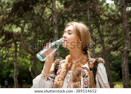Beautiful young woman in native costume drinking water