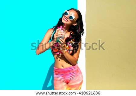 Beautiful young woman in nice summer pink outfit posing on colorful wall with ice cocktail,fresh mojito,blue hawaii. Fashion photo, nice hair, big smile.sunglasses fashion,colorful summer clothes - stock photo