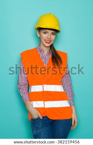 Beautiful young woman in orange reflective vest, yellow hardhat and jeans posing with hand in pocket. Three quarter length studio shot on turquoise background. - stock photo