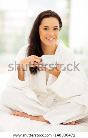 beautiful young woman in pajamas drinking coffee - stock photo