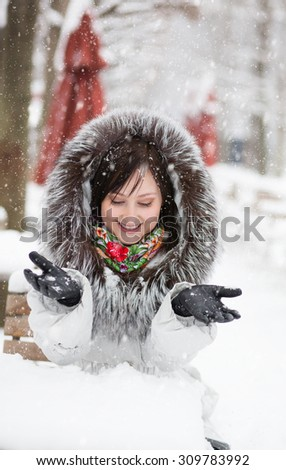 Beautiful young woman in Paris in an outdoor cafe, enjoying beautiful winter day and snow falling from the sky. Rare snowy day in Paris  - stock photo