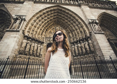 Beautiful young woman in Paris on holidays in France staying in front of Notre Dame de Paris while walking on Champs-Elysees, Paris, France - stock photo