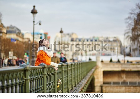 Beautiful young woman in Paris walking on the Isle of the Swans on a beautiful colorful autumn day - stock photo