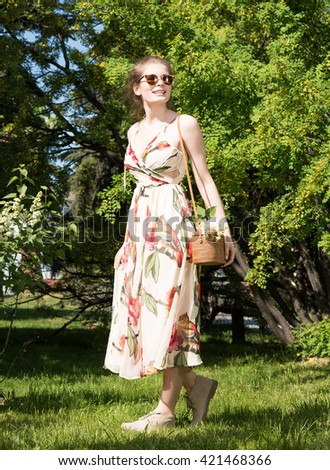 Beautiful young woman in Park in summer dress with a handbag. Sunglasses. Vertical portrait of a sweaty growth