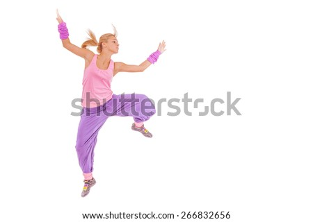 Beautiful young woman in pink dress jumping, isolated on white background.