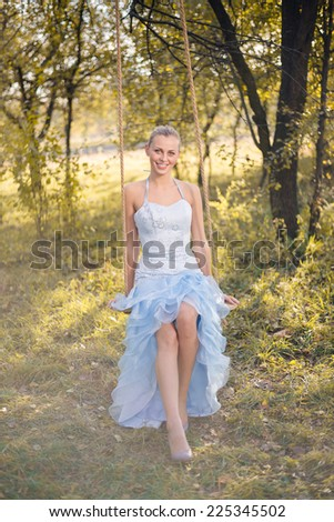 Beautiful young woman in prom dress sitting on swings on green summer or autumn outdoors copyspace background - stock photo