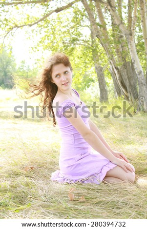 Beautiful young woman in purple dress sitting outdoors on dry spring grass against trees in park Sun light  on land Flying hair in air Windy weather Cute girl wear short violet skirt Open shoulders - stock photo
