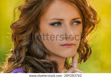 Beautiful young woman in purple dress thought, against green of summer park. - stock photo
