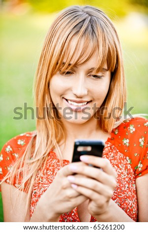 Beautiful young woman in red dress dials number on mobile phone, against summer city park. - stock photo