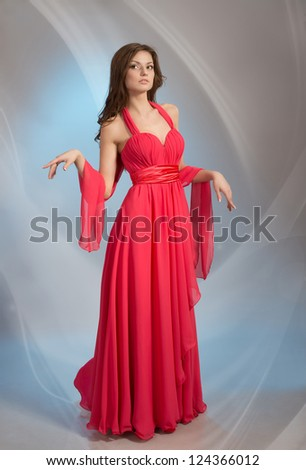 Beautiful young woman in red evening dress, on grey background