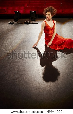 Beautiful young woman in red gown sitting on stage floor - stock photo