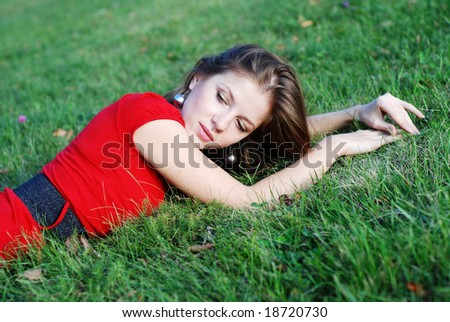 beautiful young woman in red lying on the green grass