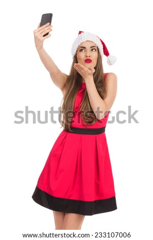 Beautiful young woman in red santa's hat and dress taking a selfie and sending a kiss. Three quarter length studio shot isolated on white. - stock photo