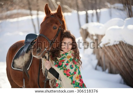 beautiful young woman in Russian national scarf with a horse in the countryside in winter - stock photo