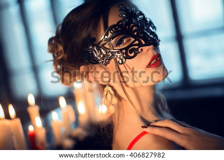 Beautiful young woman in sexy lingerie and black mask alluring in vintage apartment. Sexy girl in lingerie at night by candlelight - stock photo