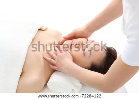 Beautiful young woman in spa. Facial massage. - stock photo