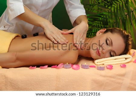 beautiful young woman in spa salon getting massage with spa stones - stock photo