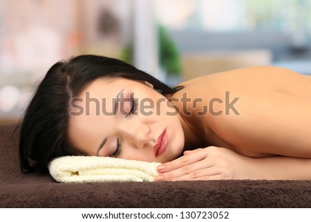 Beautiful young woman in spa salon, on bright background