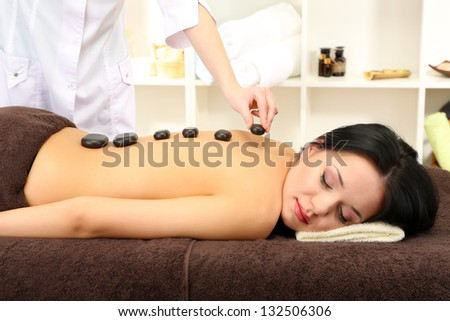 Beautiful young woman in spa salon with spa stones, on bright background