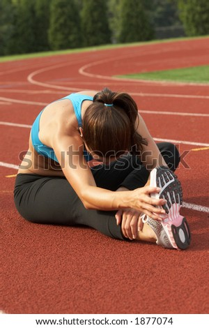 Beautiful Young Woman in Sports Bra Leaning and Stretching Leg and Hamstring - stock photo