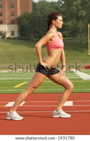 Beautiful Young Woman in Sports Bra Stretching Calf Muscles - stock photo