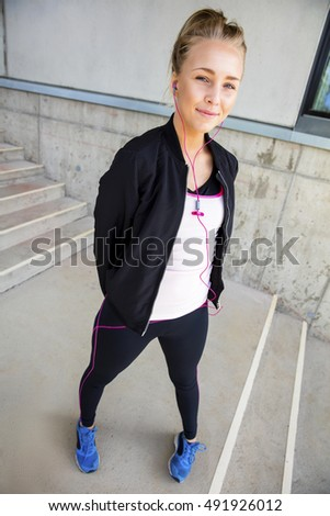 Beautiful Young Woman In Sportswear Standing On Stairway