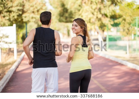 Beautiful young woman in sporty outfit jugging with her boyfriend on a running track and looking back - stock photo