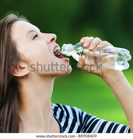 beautiful young woman in striped jacket standing in park summer drinks water from bottle - stock photo