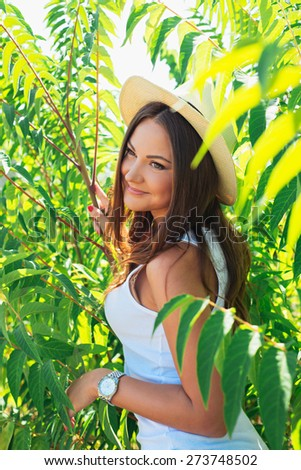 Beautiful young woman in stylish hat and jeans shorts posing. Hipster style. Summer time. girl with long hair poses in warm spring day - stock photo