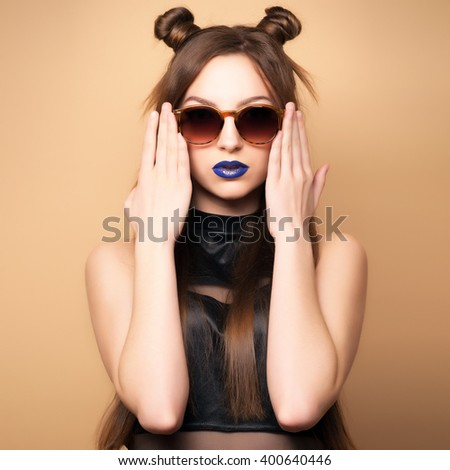 Beautiful young woman in sunglasses. Cut girl. Spring-summer outfit. Hairstyle Coachella. Short Sexy Shorts. Dark blue lipstick. Fashionable  woman . Yellow background. Toned image.