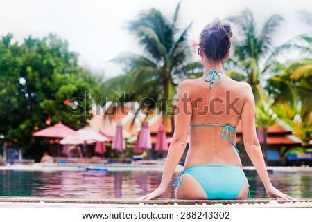 Beautiful young woman in sunglassesand straw hat near luxury pool - stock photo