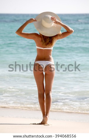 Beautiful young woman in sunhat on beach - stock photo