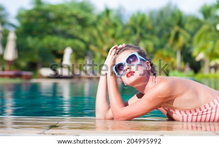 beautiful young woman in swimsuit and fancy sunglasses relaxing by the luxury pool  - stock photo