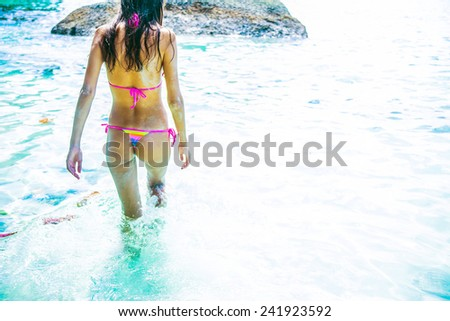 beautiful young woman in swimsuit goes into ocean in hot summer day. Rear view Cute female adult girl run in hot water texture Wet sandy full length sandy body with tanned skin Space for inscription - stock photo