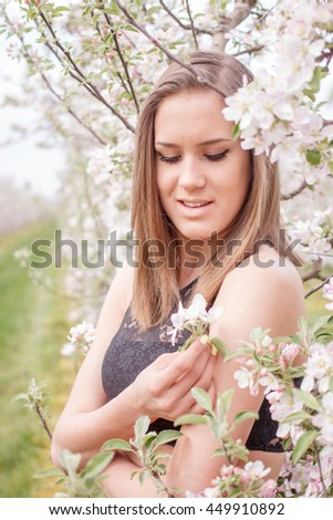 beautiful young woman in the apple garden near the apple blossom tree on a warm summer day - stock photo