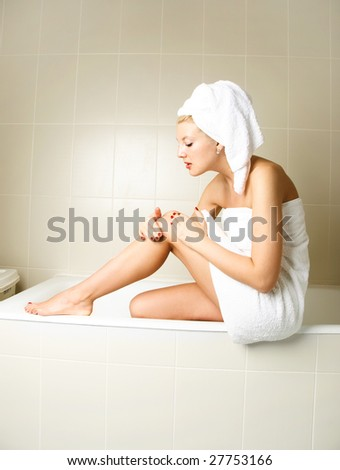 beautiful young woman in the bathroom pampering herself after the shower and applying body lotion - stock photo