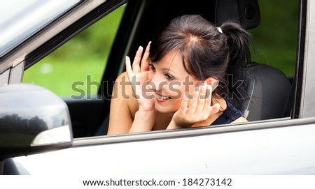 beautiful young woman in the car, looking at the mirror