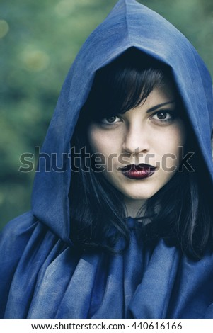 beautiful young woman in the hood in the forest