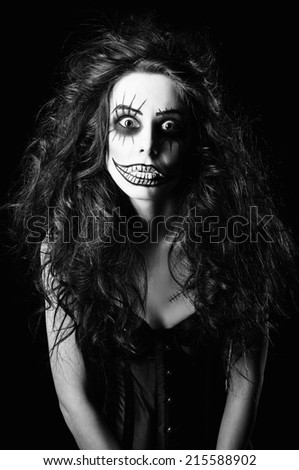 Beautiful young woman in the image of a sad gothic freak clown. Black and white - stock photo
