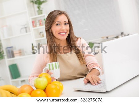 Beautiful young woman in the kitchen drinking coffee and reading recipe on laptop. Looking at camera.