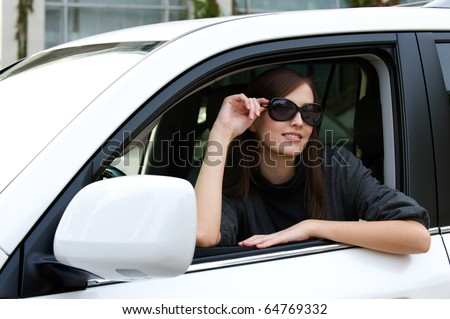 Beautiful young woman in the new car with sunglasses - outdoors - stock photo