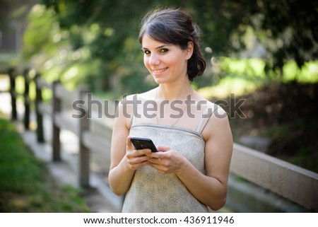 Beautiful young woman in the park texting on the phone