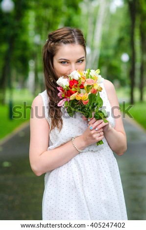 Beautiful young woman in the park with bouquet on a warm summer day after rain - stock photo