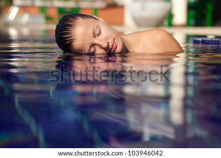 Beautiful young woman in the pool. Left half of her face and shoulder above the water - stock photo