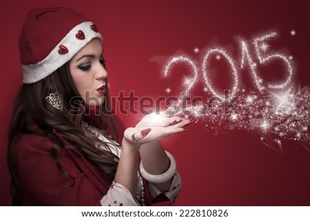 Beautiful young woman in the Santa costume blowing snowflakes and make New Year numbers 2015 - stock photo