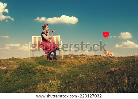 Beautiful young woman in the style of pin-up paints lips with lipstick sitting on a couch in nature. - stock photo